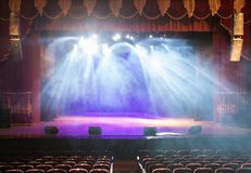 The stage of the theater illuminated by spotlights and smoke. From the auditorium Stock Images