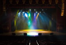 The stage of the theater illuminated by spotlights and smoke. From the auditorium Stock Photos