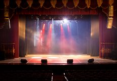 The stage of the theater illuminated by spotlights and smoke. From the auditorium Stock Image