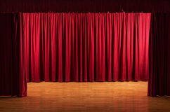 The stage - theatrical scene with red curtains. Old stage with worn floor - theatrical scene with open red curtains Stock Photography