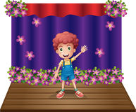 A stage with a young boy waving happily Stock Images