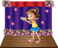 A stage with a young girl holding a camera Royalty Free Stock Photography
