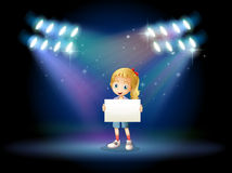 A stage with a young girl holding an empty signage Stock Photo