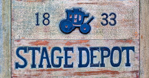 Stagecoach Sign. A stage depot sign made from wood. There is a picture of a stagecoach on it Stock Photo