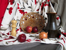 Staged still life with red, grey and white color drapery, apples Royalty Free Stock Photo