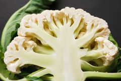 Stages of cutting cauliflower on black background, cooking backgroung. Stages of cutting cauliflower on black background. Chopping fresh vegetables, cooking royalty free stock photography
