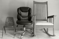Stages of Life. Chairs lined up (child's school chair, office chair, and rocking chair) representing the stages of life Stock Photography