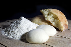 Stages of Making Bread-Flour, Dough and Loaf of Bread on Wooden Table Over Black Background Royalty Free Stock Photos