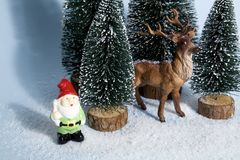 Snowy forest firs gnome and reindeer blue Stock Image