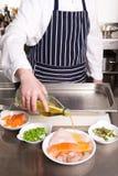 Stagione del cuoco unico con l'olio di oliva Fotografia Stock