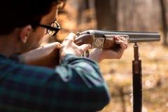 Stagione di caccia di autunno Cacciatore dell'uomo con una pistola Cercando nel legno fotografia stock