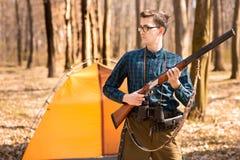 Stagione di caccia di autunno Cacciatore dell'uomo con una pistola Cercando nel legno immagine stock