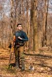 Stagione di caccia di autunno Cacciatore dell'uomo con una pistola Cercando nel legno fotografie stock