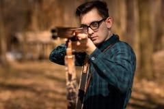 Stagione di caccia di autunno Cacciatore dell'uomo con una pistola Cercando nel legno fotografia stock libera da diritti