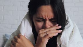 Stagione di influenza fredda, naso semiliquido Ragazza malata sul letto che starnutisce in fazzoletto in camera da letto video d archivio