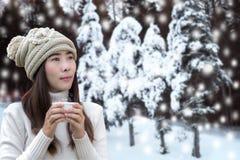 Stagione di inverno La mano del ` s della donna che tiene una tazza di caffè bianca agli alberi di Natale della neve, si rilassa  Immagini Stock Libere da Diritti