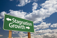 Stagnation or Growth Green Road Sign Over Clouds and Sky Royalty Free Stock Images