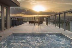 Stagno a casa del lusso di tramonto Immagine Stock
