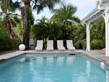 Stagno con le sedie di salotto nella regolazione tropicale fotografie stock