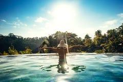 Stagno di infinito sull'isola esotica lussuosa Ritratto del cappello d'uso della ragazza che gode del sole allo stagno Immagine Stock