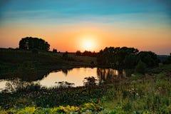 Stagno di riflessione nell'ambito del tramonto luminoso nel giorno di sera Immagine Stock