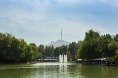 Stagno nel parco di divertimenti nel pomeriggio La torre e le montagne di Almaty TV sono nei precedenti Almaty, il Kazakistan Immagine Stock