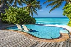 Stagno privato del oceanfront con le chaise-lounge sommerse in una località di soggiorno di lusso Fotografia Stock