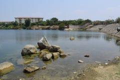 Stagno roccioso con la costruzione sulla banca di distanza Fotografie Stock Libere da Diritti