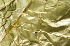Stagnola dorata strutturata e fondo Fotografia Stock