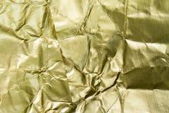 Stagnola dorata strutturata e fondo Fotografie Stock