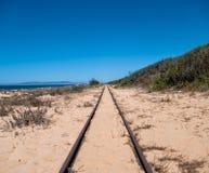 Stahlbahnstrecken auf Sand-Strand Stockbilder