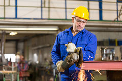 Stahlbauarbeiterausschnittmetall mit Winkelschleifer Stockfotografie