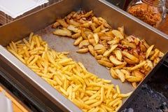 Stahlbehälter mit gebratener Kartoffel zwängt, Pommes-Frites Stockfotografie
