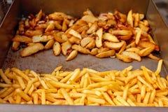 Stahlbehälter mit gebratener Kartoffel zwängt, Pommes-Frites Lizenzfreie Stockfotografie