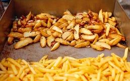 Stahlbehälter mit gebratener Kartoffel zwängt, Pommes-Frites Stockbilder