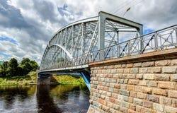 Stahlbogenbrücke auf Fluss Msta am sonnigen Sommertag Stockbild