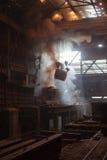 Stahlerzeugungschöpflöffel auf dem Kran, der am Stahltausendstel hängt Stockbild
