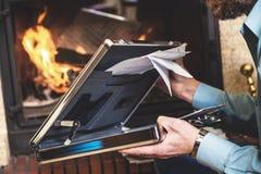 Stahlfall mit Dokumenten in den Händen des Geschäftsmannes und des Kamins Lizenzfreie Stockfotos