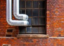 Stahlrohre außerhalb des Fensters des Backsteinbaus Stockfoto