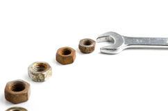 Stahlschlüsselschlüssel und viele verrostete Nüsse lokalisiert auf Weiß Lizenzfreie Stockfotos