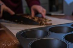 Stahltörtchenform auf einer Tabelle mit den Pekannüssen, die gehackt werden lizenzfreie stockfotografie
