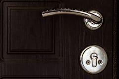 Stahltür mit dunkelbrauner Beschaffenheit Türknauf und Schlüsselverschluß stockbild