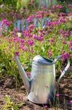 Stahlwasserkanister gegen Blumen im Sommergarten Stockfoto