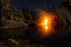 Stahlwolle-Feuer, das über felsigen See spinnt lizenzfreies stockbild