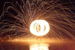 Stahlwolle-Feuer-Spinner auf Wasser Stockfotografie