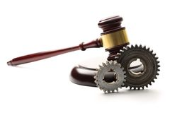 Stahlzahnräder auf dem hölzernen Hammer des Richters Lizenzfreie Stockfotografie