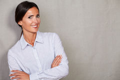 Staight hair lady with arms crossed. Staight hair lady with her arms crossed wearing button down shirt and smiling while looking at camera against grey texture Stock Image