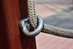 Stailess steel anchor loop. Detail of fixing the white nylon rope to the wooden beam. On the structures of the children`s playgrou royalty free stock photo