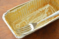 Stain of butter cake and fork in empty aluminum tray. Stain of butter cake and silver fork in empty aluminum tray royalty free stock photography