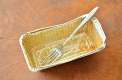 Stain of butter cake and silver fork in empty aluminum tray. On wooden table royalty free stock photo